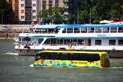 Budapest Ungern - Juni, 02, 2018 - den amfibiska bussen konkurrerar med kryssningskeppet på Danubet River Royaltyfria Bilder