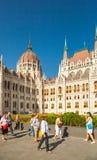 BUDAPEST UNGERN - JUNI 16, 2016: Grupp av turister som förbigår ungersk parlamentbyggnad i Budapest, Ungern - Juni 16, 2016 Arkivfoton