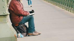 Budapest, Ungheria - 6 dicembre 2018: Un mendicante affamato si siede sull'asfalto del ponte, tiene una tazza delle elemosine e l archivi video