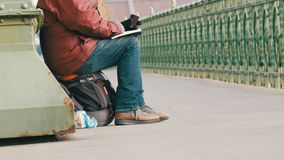 Budapest, Ungheria - 6 dicembre 2018: Un mendicante affamato si siede sull'asfalto del ponte, tiene una tazza delle elemosine e l stock footage
