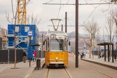 Budapest, Ungheria, il 22 marzo 2018: Tram giallo nell'inverno in anticipo con il cielo nuvoloso Il tram numero 2 è famoso per es immagine stock libera da diritti
