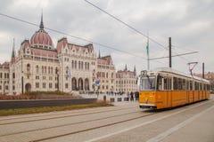 Budapest, Ungheria, il 22 marzo 2018: Tram giallo nell'inverno in anticipo con il cielo nuvoloso Il tram numero 2 è famoso per es fotografia stock libera da diritti