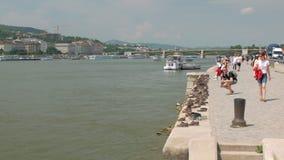 Budapest, Ungheria - MAGGIO 2018: i turisti stanno osservando le scarpe del monumento sulla Banca del Danubio stock footage