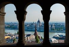 Budapest y opinión húngara del parlamento a través del arco del bastión del ` s del pescador - Hungría fotos de archivo libres de regalías