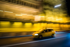 Budapest yellow cab. Blured budapest yellow cab by Hungarian Parliament iluminated by night Royalty Free Stock Images