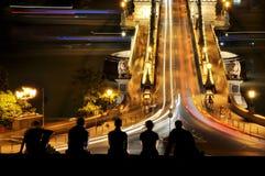Budapet铁锁式桥梁的青年人在晚上 库存图片
