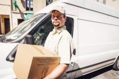 Budbärare Delivering Parcel som står bredvid hans skåpbil Royaltyfri Fotografi