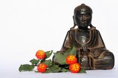 Budda buddha  flowers. Isolated budda with orange flowers,Flower composition and wood carving buddha Royalty Free Stock Images