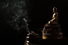 Budda de bronce que se sienta con la hornilla de incienso Foto de archivo