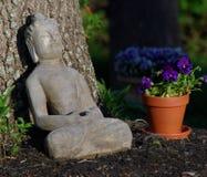 Budda-Statue, die gegen einen Baum an einem sonnigen Tag stillsteht Stockbild