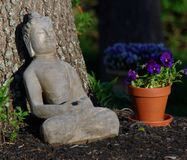 Budda statue resting against a tree on a sunny day. Purple flowers clay Stock Image