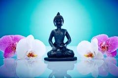 Buddah avec des orchis roses et blancs Photographie stock