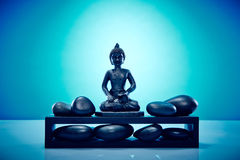 Buddah on a plattform with zen stones. Wellness and Spa Image, works perfect for advertising Health and Beauty, Spirituality or Massage Royalty Free Stock Photography