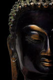 Buddah statue. Buddhist statue with golden details against black Stock Image