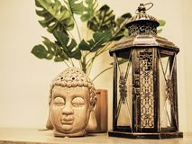 Buddah statue in modern home, Home decoration. Candle Lighter and Buddha Head statue and Monstera's Leaves. Holidays decoration.  stock images
