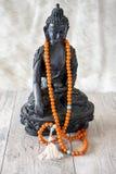 Buddahstandbeeld met oranje parels voor lezingsmantras Stock Fotografie