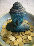 Buddha 1. A tarnished copper Buddha sculpture in a bowl with gold coin donations stock photography