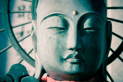 Buddha. Smiling buddha in close-up. Cross processed Royalty Free Stock Photography