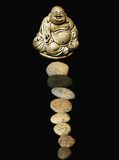 Buddha. Statuette of smiling buddha with stones before it Stock Photo