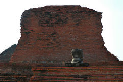 A Buddha against a wall. An old, headless Buddha sitting in front of a crumbling wall of a temple Royalty Free Stock Photography