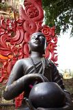 Buddha black statue with Red Caduceus. A unique happy buddha statue holding a buddhist begging bowl wearing a robe and mala with his eyes open and a red caduceus stock photos