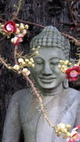 Buddha with blooming flowers in front of tree. Seated smiling Buddha statue with blooming flowers  in front of the old tree Stock Photo