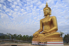 Buddha in the blue sky. Golden statue of Buddha in the blue sky Stock Image