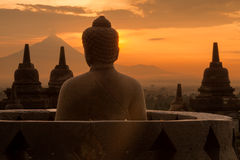 Buddha at Borobudur. A buddha statue at the Borobudur looks out to the distant volcano at sunrise Stock Photography