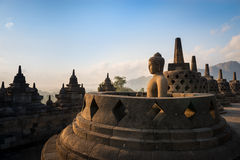 Buddha in Borobudur Temple at sunrise. Indonesia. Buddha statue in open stupa in Borobudur, or Barabudur, temple Jogjakarta, Java, Indonesia at sunrise. It is a Stock Images