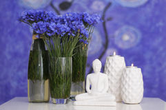 Buddha. Bouquet of cornflowers with the statuette of the Buddha and candles. Blue background Stock Images