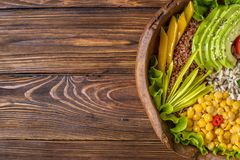 Buddha bowl with chickpea, avocado, wild rice, quinoa seeds, bell pepper, tomatoes, greens, cabbage, lettuce on brown burnt wooden stock images