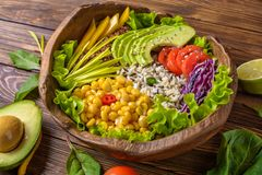 Buddha bowl with chickpea, avocado, wild rice, quinoa seeds, bell pepper, tomatoes, greens, cabbage, lettuce on brown burnt wooden royalty free stock photography