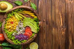 Buddha bowl with chickpea, avocado, wild rice, quinoa seeds, bell pepper, tomatoes, greens, cabbage, lettuce on brown burnt wooden stock photos
