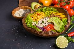 Buddha bowl with chickpea, avocado, wild rice, quinoa seeds, bell pepper, tomatoes, greens, cabbage, lettuce on dark stone table stock image