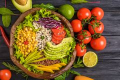 Buddha bowl with chickpea, avocado, wild rice, quinoa seeds, bell pepper, tomatoes, greens, cabbage, lettuce on old black wooden. Buddha bowl with chickpea royalty free stock photos