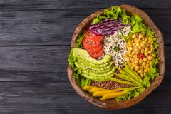 Buddha bowl with chickpea, avocado, wild rice, quinoa seeds, bell pepper, tomatoes, greens, cabbage, lettuce on old black wooden stock photography