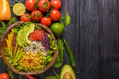 Buddha bowl with chickpea, avocado, wild rice, quinoa seeds, bell pepper, tomatoes, greens, cabbage, lettuce on old black wooden royalty free stock image