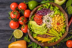 Buddha bowl with chickpea, avocado, wild rice, quinoa seeds, bell pepper, tomatoes, greens, cabbage, lettuce on old black wooden stock photo