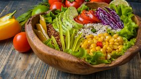 Buddha bowl with chickpea, avocado, wild rice, quinoa seeds, bell pepper, tomatoes, greens, cabbage, lettuce on old shabby wooden stock photos
