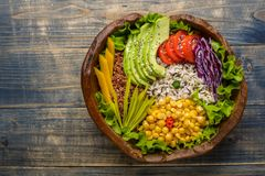 Buddha bowl with chickpea, avocado, wild rice, quinoa seeds, bell pepper, tomatoes, greens, cabbage, lettuce on old shabby wooden. Buddha bowl with chickpea stock images