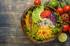 Buddha bowl with chickpea, avocado, wild rice, quinoa seeds, bell pepper, tomatoes, greens, cabbage, lettuce on old shabby wooden royalty free stock photography