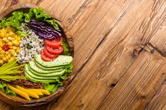 Buddha bowl with chickpea, avocado, wild rice, quinoa seeds, bell pepper, tomatoes, greens, cabbage, lettuce on old wooden table. stock images