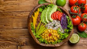 Buddha bowl with chickpea, avocado, wild rice, quinoa seeds, bell pepper, tomatoes, greens, cabbage, lettuce on old wooden table. royalty free stock photo