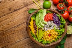 Buddha bowl with chickpea, avocado, wild rice, quinoa seeds, bell pepper, tomatoes, greens, cabbage, lettuce on old wooden table. royalty free stock photography