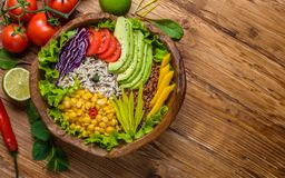 Buddha bowl with chickpea, avocado, wild rice, quinoa seeds, bell pepper, tomatoes, greens, cabbage, lettuce on old wooden table. Top view with copy space royalty free stock photography