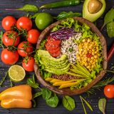 Buddha bowl with chickpea, avocado, wild rice, quinoa seeds, bell pepper, tomatoes, greens, cabbage, lettuce on old wooden table. Top view with copy space royalty free stock photo