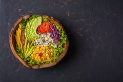 Buddha bowl with chickpea, avocado, wild rice, quinoa seeds, bell pepper, tomatoes, greens, cabbage, lettuce on shabby dark stone stock image