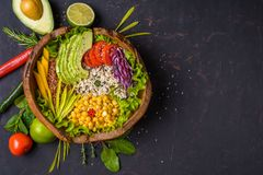 Buddha bowl with chickpea, avocado, wild rice, quinoa seeds, bell pepper, tomatoes, greens, cabbage, lettuce on shabby dark stone royalty free stock images