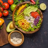 Buddha bowl with chickpea, avocado, wild rice, quinoa seeds, bell pepper, tomatoes, greens, cabbage, lettuce on shabby dark stone stock photos