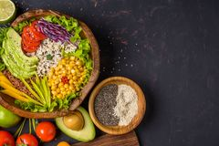 Buddha bowl with chickpea, avocado, wild rice, quinoa seeds, bell pepper, tomatoes, greens, cabbage, lettuce on shabby dark stone royalty free stock photo